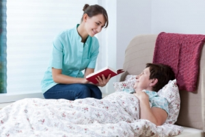 caregiver reading books to senior woman