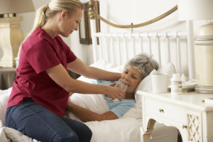 nursing aide assisting senior woman in drinking water